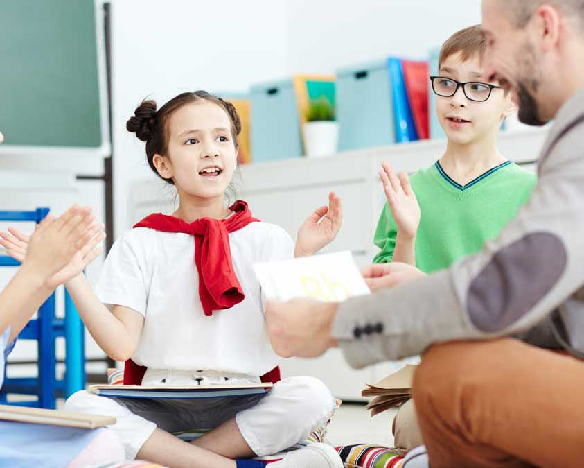 close up image of students sitting on the floor clapping